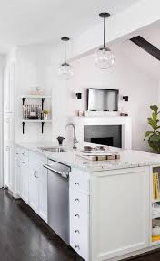 lovely kitchen features a white peninsula topped with white granite fitted with a curved stainless steel sink and gooseneck faucet next to a stainless steel