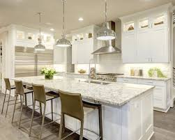 Kitchen with white cabinets and black granite countertops with wood flooring