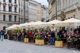 Banque dimages krakow poland may 25 2017 outdoor restaurant near residential homes there are many people who seat under a patio umbrellas