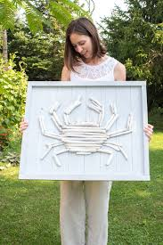 woman standing outdoors holding a diy driftwood crab wall art as an example of lake house