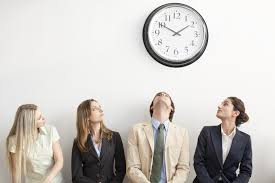 interviewing state university interviewees look up at a clock on the wall