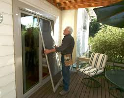 worker is working on replacement screen door in patio for modern home