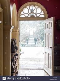 open front door. View Looking Out Of Open Front Door With Fan Light To Snowy Garden Path -  Stock T