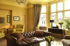 elegant curtains for living room with yellow walls and brown leather sofa as well as crystal chandelier