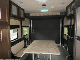 the queen is tucked across the trailer in the hyper lite xlr 27 with a nightstand for storing your essentials
