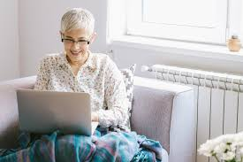 senior woman glasses laptop couch INF