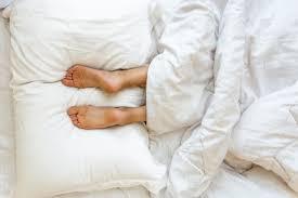 image of feet on pillows microfiber sheets vs cotton