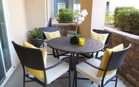 posite patio furniture with small wicker patio table and brick pattern wall fence