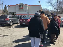 to enlarge a line snakes around the parking lot of the little caesars in ferndale ahead of monday s