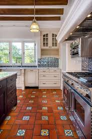Spanish Style kitchen features 3 light windows, terracotta floor with  glazed accent inserts, blue/white backsplash tiles, off white cabinets with  arch upper ...
