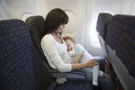 flying with a baby or toddler baby girl sleeping on mother s laps while traveling on