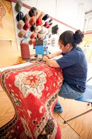 a dalworth rug cleaning specialist works at a sewing machine repairing a rug