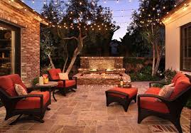 traditional backyard design with stone patio tile with exclusive outdoor led string lights and stylish black chairs using orange cushions