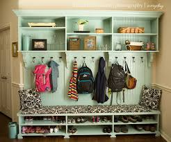 Mudroom wall that has space for shoes, bench for sitting, hooks for ...
