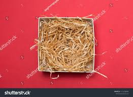opened gift box with decorative straws fillers on red background