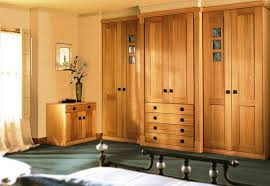 large brown wooden wardrobes with six doors and low drawers mounted on ivory wall and charcoal carpet floor