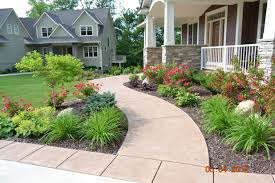 Beautiful example of curved sidewalk and large planting beds creating  interest to those entering the house