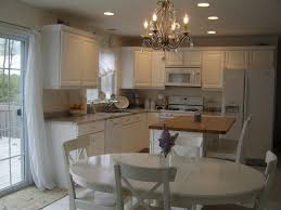 shabby sheek kitchen design with paint kitchen cabinets and oval dining table plus chandelier