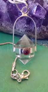 a beautiful clear herkimer diamond crystal pendant in a silver setting there is a red ruby garnet mounted on the front of the pendant