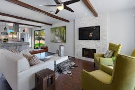 contemporary living room with exposed beam hardwood floors stone fireplace faux wood beams