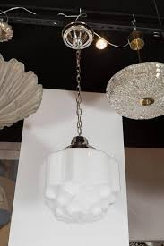 this art deco pendant chandelier is made of hand molded white milk glass with skyser details