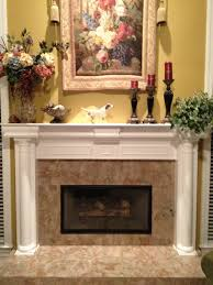 interior brown marble and white fireplace mantel with shelf above with red candles on the