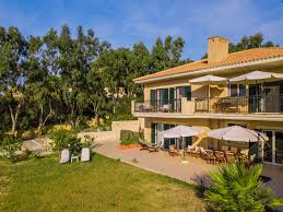 beach apartments in kefalonia a villa with green garden tall trees and white umbrellas
