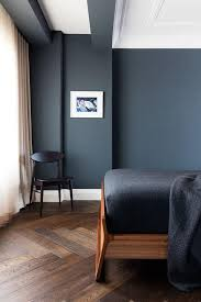 Dark gray matte wall paint color bedroom with a dark hardwood herringbone  floor, walnut wood