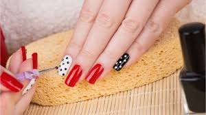 applying nail art to hands with red white and black nail polish