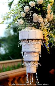 four tier chandelier wedding cake hanging upside down on a stand the cake was decorated with sugar flowers silver studded ribbons crystals