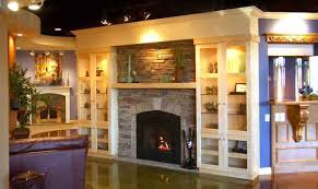 this display was shows a fireplace faced with a manmade stack stone with built with cabinets