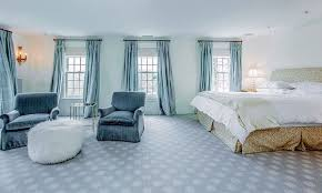 white carpet bedroom. large contemporary bedroom with sitting area and flowing blue curtains carpet white walls a