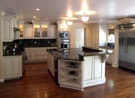 engaging white glass front kitchen cabinets with black countertop and white ceiling mounted kitchen lamp also
