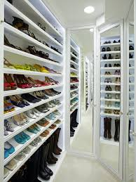 stylish narrow walk in closet design idea featuring floor to ceiling white wooden wall shoe rack