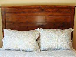 a wooden headboard on a made up bed