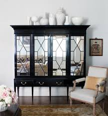 black armoire accented with mirrored doors atop sleek legs topped with a collection of white pottery alongside a bergere chair atop a gold persian rug