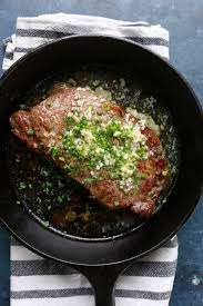 overhead photo of steak topped with er garlic and chives in a cast iron