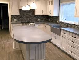curved concrete countertops on kitchen island with white cabinets