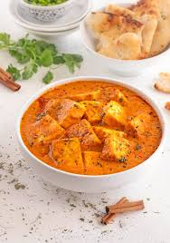 creamy paneer er masala gravy in white bowl with naan bread at the back