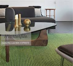 glass coffee table and green area rug in modern living room stock photo
