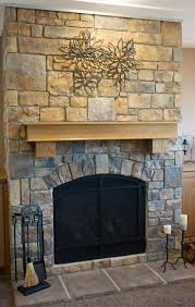 stone fireplace with irregular surfaces using ceiling track as an art hanging system