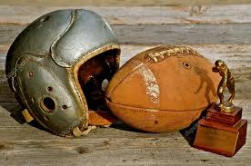 a chin strapless helmet and old leather football serve to bring memories of football of a past era photo by fiskness
