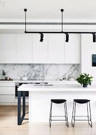 Black and white monochrome kitchen: handleless white cabinets and  benchtops, grey marble splashback,