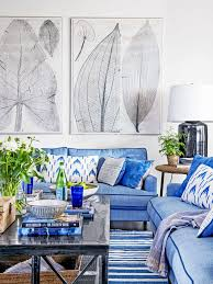 royal blue linen fiber convertible sofa with white blue pillows black wood coffee table floral painted wall art black glass large table lamp with white  on royal blue and white wall art with area rugs royal blue linen fiber convertible sofa with white