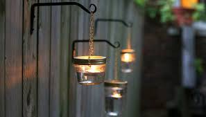 transform mismatched mason jars into simple fence mounted outdoor lighting