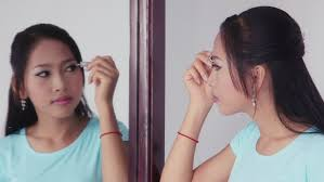 looking in mirror sad. young people, woman, lifestyle and beauty, beautiful asian girl applying makeup to eyes looking in mirror sad