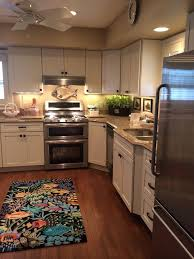 minimalist coastal kitchen decor with l shaped marble countertop and glass fish accessory under white kitchen cabinet plus stainless steel refrigerator
