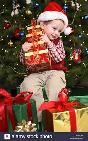 Two year old boy opening presents on Christmas morning Stock Photo