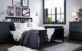 a large bedroom with a black brown bed with bed textiles in beigewhite bedroom furniture in ikea