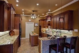 tan wall color with dark finished wooden cabinet using marble countertop for excellent kitchen design using small recessed lighting ideas